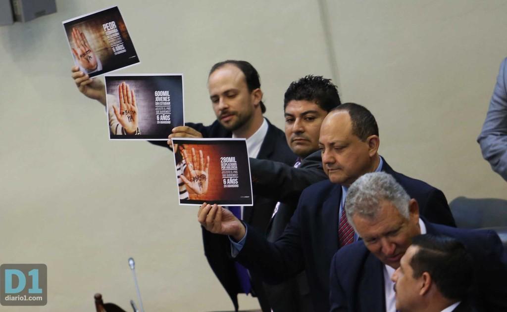 Al finalizar el discurso, diputados suplentes de ARENA protestaron con carteles en la sesión solemne donde el presidente ofreció su discurso. Foto D1: Nelson Dueñas