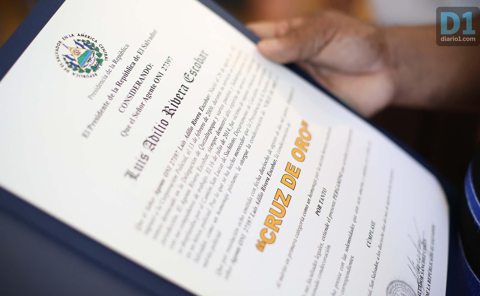 Diploma que el presidente Sánchez Cerén entregó a familiares de policías asesinados, en las manos de una hija huérfana. Foto: D1. Nelson Dueñas.