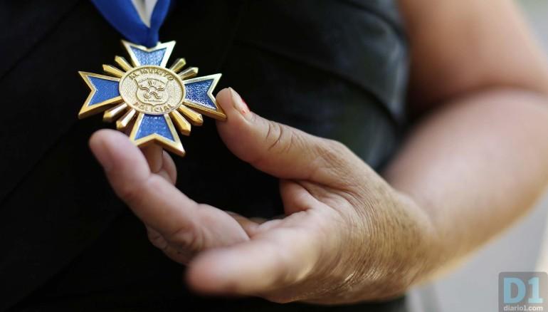 """Esposa de un agente fallecido sostiene la """"cruz de oro"""" que le entregó el presidente salvadoreño como reconocimiento a la memoria de su difunto esposo. Foto: D1. Nelson Dueñas."""
