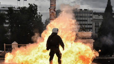 A firebomb explodes beside a riot police member during a massive protest on February 4, 2016. Thousands of people marched across Greece on February 4, 2016 as diverse classes united in a crippling general strike over a pension overhaul that has sparked a major backlash against embattled leftist Prime Minister Alexis Tsipras. / AFP / ARIS MESSINIS