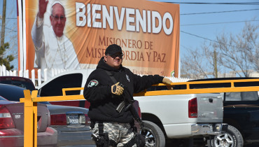 A prison guard stands in front of a banner welcoming Pope Francis at the main entrance of the city prison in Ciudad Juarez, Mexico, on February 3, 2016. Pope Francis will visit Ciudad Juarez's prison to meet with inmates during the last stage of his tour along four Mexican states from February 12 to 17.   AFP PHOTO/ Yuri CORTEZ / AFP / YURI CORTEZ