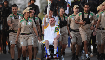 Former PM mounted militarized police sargent Helvio Pompilio accompanied by an escort of National Force elite police national unit personnel, carries the Olympic Torch in Brasilia, on May 3,m 2016. Embattled President Dilma Rousseff greeted the Olympic flame in Brazil on Tuesday, promising not to allow a raging political crisis, which could see her suspended within days, to spoil the Rio Games. / AFP PHOTO / EVARISTO SA