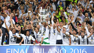 Real Madrid's Spanish defender Sergio Ramos (C) lifts the trophy as Real Madrid players celebrate winning the UEFA Champions League final football match over Atletico Madrid at San Siro Stadium in Milan, on May 28, 2016. / AFP PHOTO / GERARD JULIEN