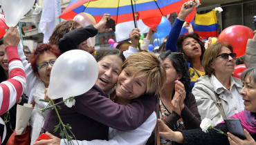 Colombians celebrate in downtown Bogota as they watch on a giant screen the signing of the ceasefire betwwen the Government and the FARC guerrillas in Havana, on June 23, 2016.  Colombia's government and the FARC guerrilla force signed a definitive ceasefire Thursday, taking one of the last crucial steps toward ending Latin America's longest civil war. / AFP PHOTO / Guillermo Legaria