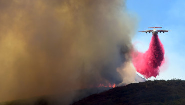 A chopper drops fire retardant in the mountains off Placerita Canyon Road in Santa Clarita, California on July 25, 2016, to fight the the fast-moving Sand Fire which continued raging across drough-ravaged terrain in the mountains north of Los Angeles, scorching more than 33,000 acres and destroying at least 18 homes. / AFP PHOTO / Frederic J. BROWN