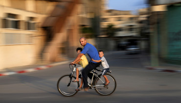 A Palestinian man rides a bike with his children at the Al-Shatee refugee camp in Gaza City, on August 29, 2016. / AFP PHOTO / MOHAMMED ABED