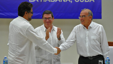 Colombian government head of delegation for peace talks Humberto de la Calle (R) and FARC-EP Commander Ivan Marquez (L) shake hands upon the signing of the agreement at the conclusion of the peace talks in Havana at the Convention Palace in Havana, on August 24, 2016. At center Cuban Foreign Minister Bruno Rodriguez. Colombia's government and FARC rebels announced Wednesday that they have reached a historic peace accord to end their half-century civil war, the last major armed conflict in the Americas. / AFP PHOTO / YAMIL LAGE