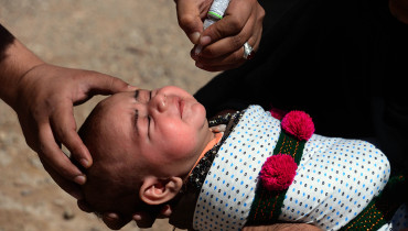 An Afghan health worker administers polio drops to a child during a polio vaccination campaign in Herat province on August 29, 2016.    Afghanistan launched a polio vaccination campaign on August 29, aimed at reaching children in areas previously controlled by Islamic State group militants, officials said.  / AFP PHOTO / AREF KARIMI