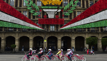 "People enjoy a ""multi rider"" bicycle along Mexico City's Zocalo during ""World Carfree Day"", on September 22, 2016. / AFP PHOTO / RONALDO SCHEMIDT"