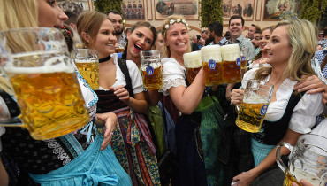 A waitress (C) carries beer mugs during the opening of the Oktoberfest beer festival in a festival tent at the Theresienwiese in Munich, southern Germany, on September 17, 2016. The World's largest beer festival Oktoberfest will run until October 3, 2016. / AFP PHOTO / CHRISTOF STACHE