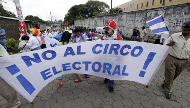 """Daniel Ortega's government opponents hold a banner that reads """"No to the electoral circus"""" during a protest demanding fair elections at Diriamba city, some 40 kilometres from Managua on October 16, 2016. Nicaragua will celebrate presidential elections on November 6, with incumbent Ortega widely seen as the favourite. / AFP PHOTO / INTI OCON"""