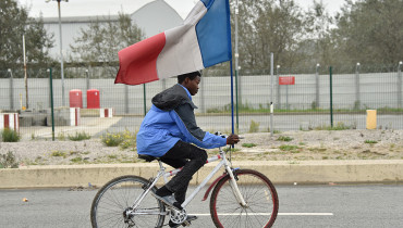 """A young migrant holding a French national flag rides a bike at the """"Jungle"""" migrant camp in Calais, on October 24, 2016. French authorities began on October 24, 2016 moving thousands of people out of the notorious Calais Jungle before demolishing the camp that has served as a launchpad for attempts to sneak into Britain. Migrants lugging meagre belongings boarded buses taking them away from Calais' """"Jungle"""" under a French plan to raze the notorious camp and symbol of Europe's refugee crisis. / AFP PHOTO / PHILIPPE HUGUEN"""