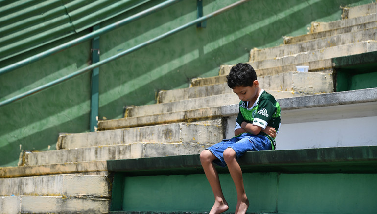 A boy sits alone on the stands during a tribute to the players of Brazilian team Chapecoense Real who were killed in a plane accident in the Colombian mountains, at the club's Arena Conda stadium in Chapeco, in the southern Brazilian state of Santa Catarina, on November 29, 2016. Players of the Chapecoense were among 81 people on board the doomed flight that crashed into mountains in northwestern Colombia, in which officials said just six people were thought to have survived, including three of the players. Chapecoense had risen from obscurity to make it to the Copa Sudamericana finals scheduled for Wednesday against Atletico Nacional of Colombia.  / AFP PHOTO / Nelson ALMEIDA