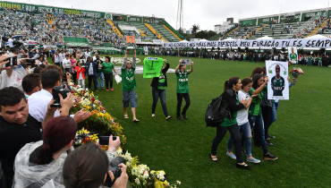Relatives of the members of the Chapecoense Real football club team killed in a plane crash in Colombia enter the field during a funeral ceremony at the stadium in  Chapeco, Santa Catarina, southern Brazil, on December 3, 2016.  The bodies of 50 players, coaches and staff from a Brazilian football team tragically wiped out in a plane crash in Colombia arrived home Saturday for a massive funeral. / AFP PHOTO / Nelson Almeida