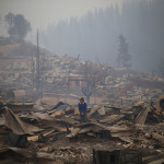 People walk amid the remains of their burnt down houses after a forest fire in Santa Olga, 240 km south of Santiago, on January 26, 2017.   Six people -- among them four firefighters and two police -- have now been killed battling vast forest fires in central Chile, officials said Wednesday. Multiple blazes have ravaged 238,000 hectares (588,000 acres) and are growing, the National Forestry Corporation said in a statement. / AFP PHOTO / PABLO VERA LISPERGUER