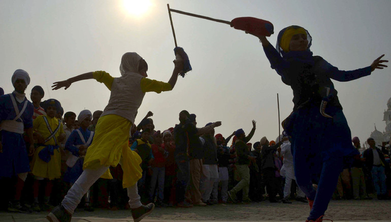 Young Indian Sikhs perform 'Gatka' the Sikh martial art during a procession from Sri Akal Takht Sahib at The Golden Temple in Amritsar on January 4, 2017, on the eve of  350th birth anniversary of the tenth Sikh Guru Gobind Singh. / AFP PHOTO / NARINDER NANU