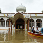 Malaysian Muslims men travel by boat after Friday prayers, outside a mousque on a flooded street in Bendang Pak Yong, Malaysia's northeastern town of Tumpat, which borders with Thailand on January 6, 2017.   Floods continued to inundate two northeast Malaysian states on January 5, as thousands of people remained in relief centres while others expressed fears of looting and sought aid. / AFP PHOTO / MOHD RASFAN