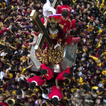 Devotees watch as a replica of the Black Nazarene is carried along a road during a procession in Manila on January 7, 2017. Hundreds of thousands of barefoot devotees will on January 9 attend the annual religious procession in one of the world's biggest Catholic parades honoring an ebony statue of Jesus Christ they believe has miraculous powers. / AFP PHOTO / Noel CELIS