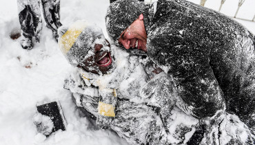 People play in the snow at Taksim square during snowfall in Istanbul on January 7, 2017.  A heavy snowstorm paralysed life in Istanbul with hundreds of flights cancelled and the Bosphorus closed to shipping traffic. The snowstorm dumped almost 40 centimetres (16 inches) of snow in parts of the Turkish metropolis overnight, causing havoc on roads as travellers sought to leave the city for the weekend getaway. / AFP PHOTO / YASIN AKGUL