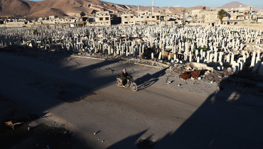A Syrian man rides a motorbike past a cemetery in the rebel-held town of Douma, on the eastern outskirts of Damascus, on January 3, 2017. / AFP PHOTO / Abd Doumany
