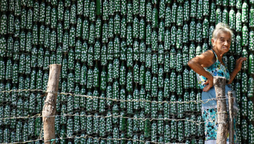 Eighty-six-year-old Maria Ponce, stands outside her house -- made out of plastic bottles -- in the village of El Borbollon, El Transito, west of San Salvador, on March 14, 2017. Maria built her house out of plastic bottles 12 years ago because she could not afford to build a conventional home. / AFP PHOTO / Marvin RECINOS