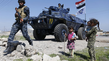 Displaced Iraqi children, who fled their homes in the Old City in western Mosul due to the ongoing fighting between government forces and Islamic State (IS) group fighters, are seen looking towards a security forces member ahead of being taken to the Hammam al-Alil camp, south of Mosul, on March 27, 2017. Iraqi forces renewed their assault against jihadists in Mosul's Old City, after days in which the battle was overshadowed by reports of heavy civilian casualties from air strikes. / AFP PHOTO / AHMAD GHARABLI
