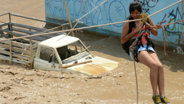 Residents of the Huachipa populous district, east of Lima, are helped on March 17, 2017, by police and firemen rescue teams to cross over flash floods hitting their neighbourhood and isolating its residents. The climatic phenomenon El Niño is causing muddy rivers overflows on the entire Peruvian coast, isolating hundreds of people, mostly residents of Lima's industrial belt neighbourhoods. / AFP PHOTO / CRIS BOURONCLE