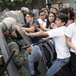 "Venezuelan opposition activists scuffle with National Guard personnel in riot gear during a protest in front of the Supreme Court in Caracas on March 31, 2017.  Venezuela's attorney general Luisa Ortega surprisingly broke ranks with President Nicolas Maduro on Friday, condemning recent Supreme Court rulings that consolidated the socialist president's power as a ""rupture of constitutional order."" / AFP PHOTO / STR"