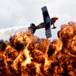 A member of the Tinstix of Dynamite aerobatics team flies in front of a wall of fire during the Australian International Airshow in Melbourne on March 5, 2017.  The annual event sees 180,000 visitors over the 3-day public event held at the Avalon Airfield some 80kms south-west of Melbourne. / AFP PHOTO / MAL FAIRCLOUGH