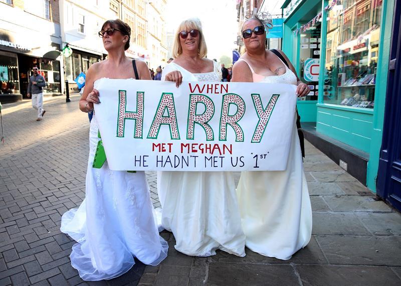 """Mujeres que sostienen un rótulo que dice: """"Cuando Enrique conoció a Meghan, no nos había conocido a nosotras primero"""". Foto D1, EFE."""