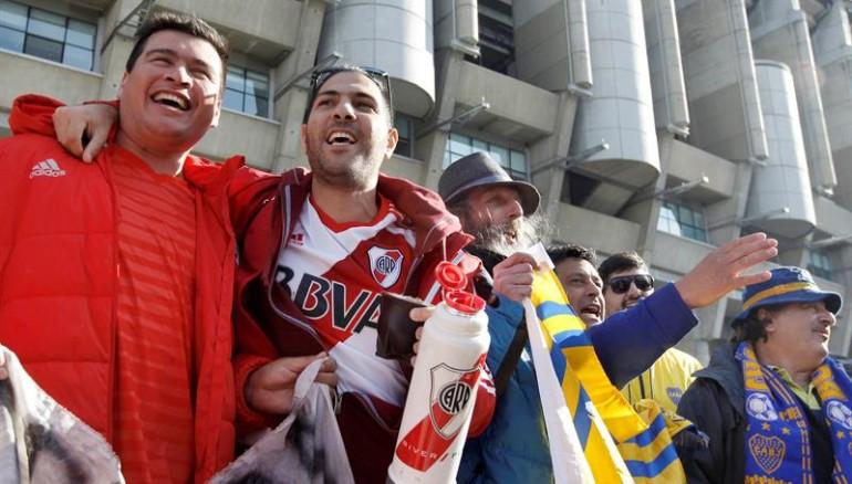 Aficionados de Boca Juniors y River Plate comparten juntos en las afueras del estadio Santiago Bernabéu. Foto: EFE.