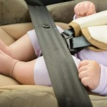 Safety concept, protection of child in travel, children feet in baby seat. Small newborn baby sitting in special car seat with safety seatbelts