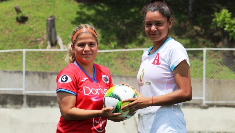 Zulia Menjívar, de FAS, y Alejandra Herrera, de Alianza, posan con el balón.