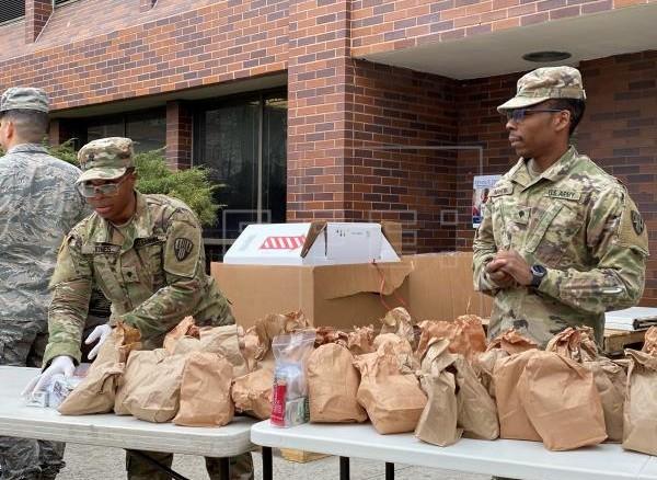 Miembros de la Guardia Nacional distribuyen alimentos este jueves en un centro comunitario de New Rochelle, Nueva York (EE.UU). La localidad de New Rochelle, al norte de la ciudad de Nueva York y mayor foco de coronavirus del estado, aplica medidas de contención en un radio de 1,6 kilómetros.  Foto de EFE.