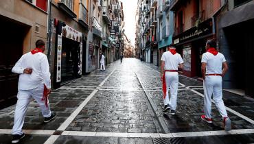 Tres corredores caminan por una vacía calle. Debido a la pandemia, la feria del toro, al igual que el resto de actos festivos, han sido suspendidos. FOTO: EFE